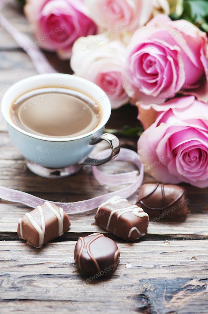 Rosa Rosen, Kaffee und Schokolade auf dem Holztisch