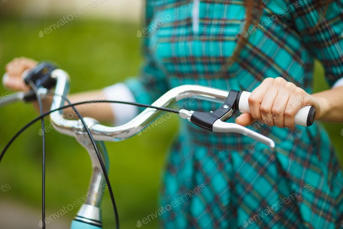 Girl walking with her bicycle outdoors