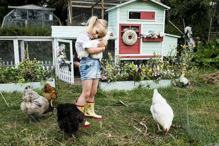 Blond girl standing in a garden in front of hen house, holding white chicken.