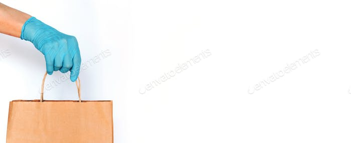 Hand in medical glove gives craft box over white background. Contactless online shopping concept