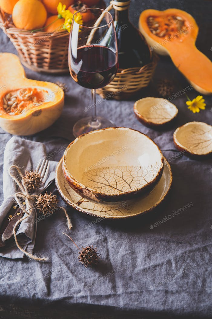 Autumn table setting with pumpkins, basket and red wine. Fall home decoration for festive dinner.