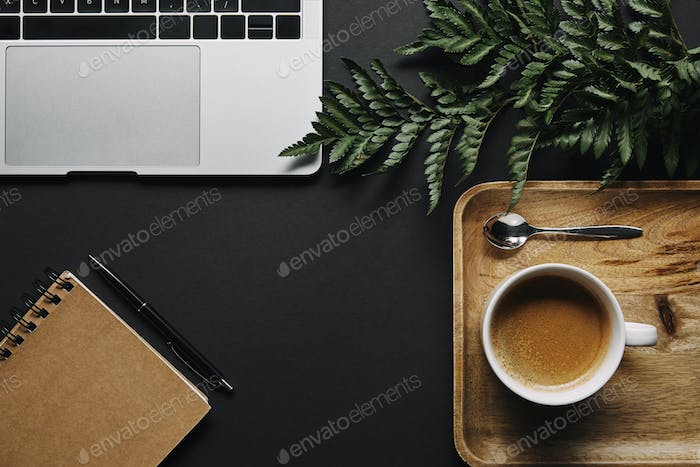 flat lay with Cup of coffee and notepad by laptop on black background