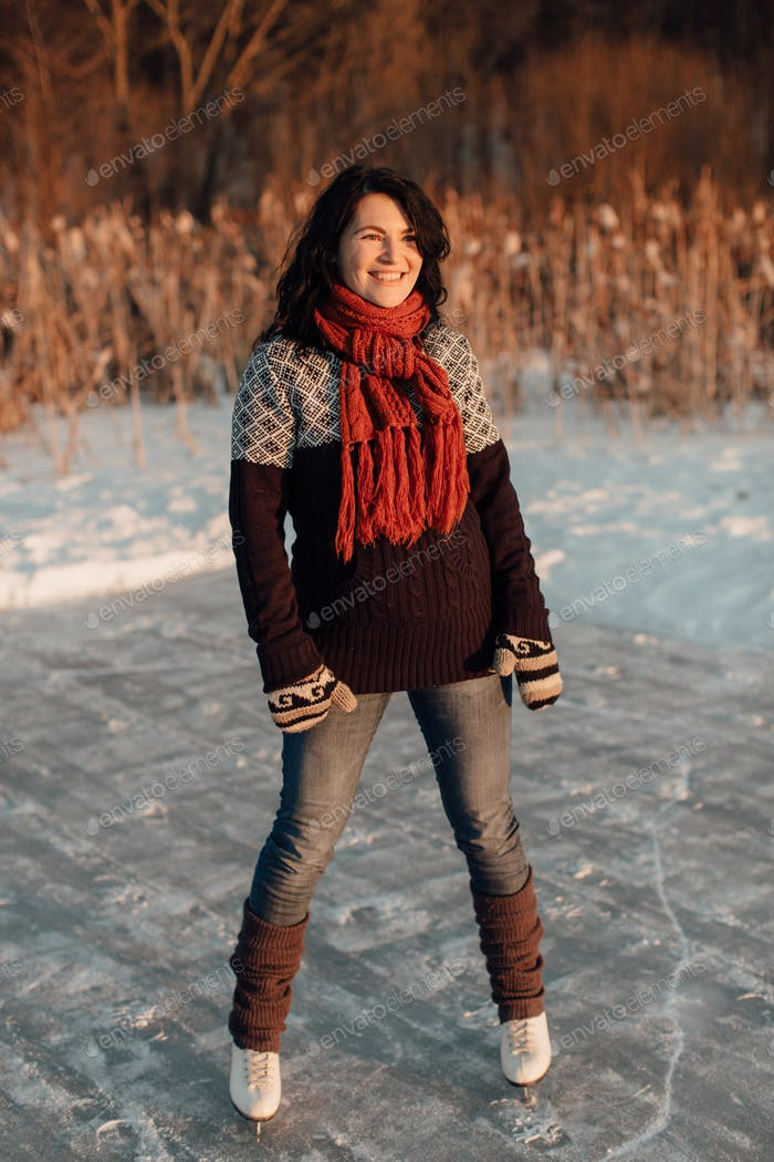 Happy woman enjoying ice skating on a frozen lake