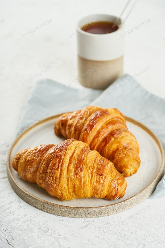 Two delicious croissants on plate and hot drink in mug. Morning French breakfast