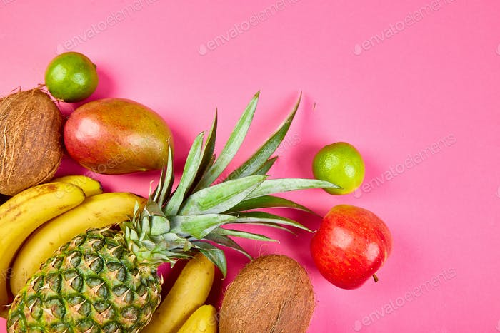 Flat lay of exotic fruits on pink background.