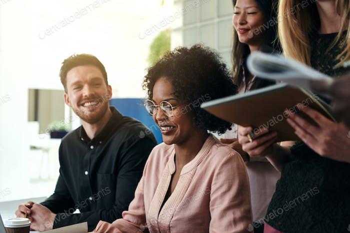 Lächelnde Gruppe von diversen Geschäftslehern, die in einem Büro zusammenarbeiten
