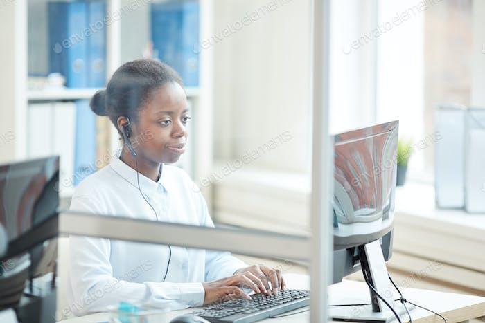 African-American Secretary Wearing Headset in Office