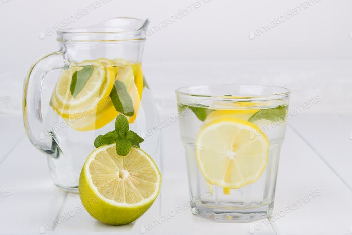 Healthy lemonade from lemon, lime and mint on white table