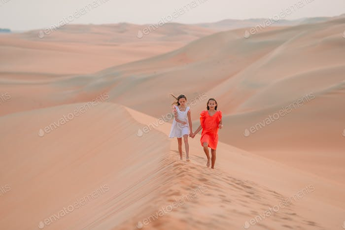 Girls among dunes in Rub al-Khali desert in United Arab Emirates