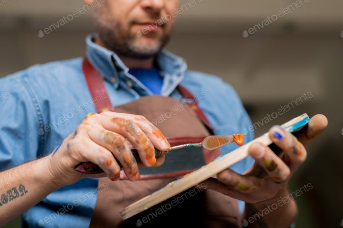 Professional creative painter holding palette while mixing colors or oil paints