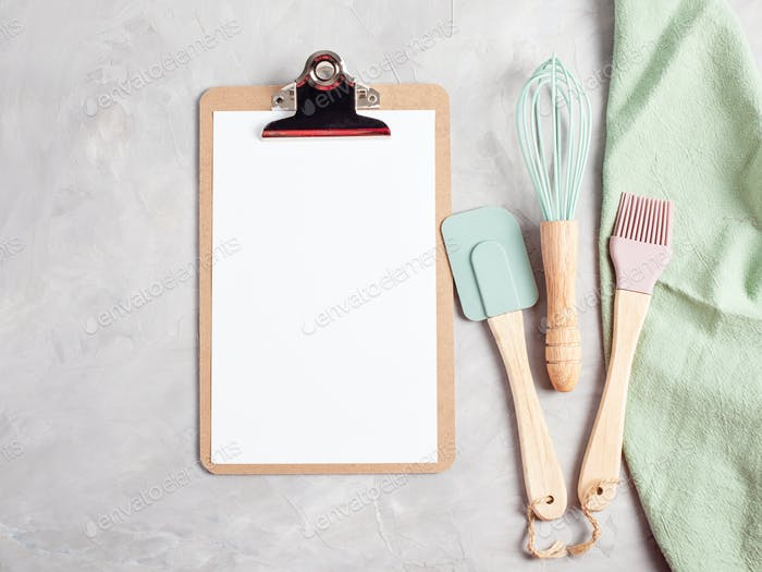 Paper clipboard with empty space and kitchen utensils top view