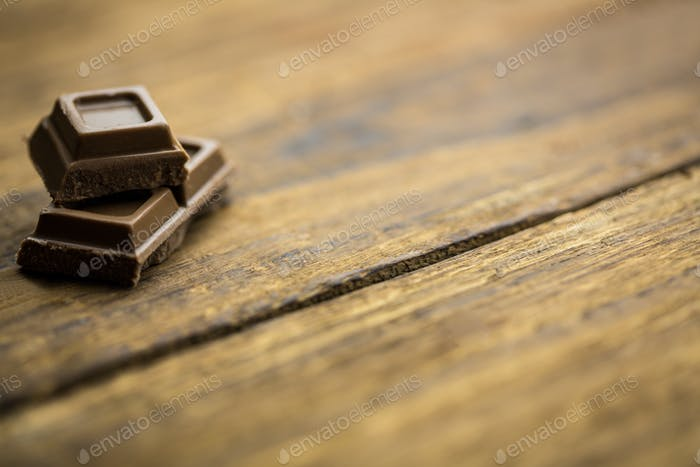 Close up view of pieces of chocolate on a wooden table