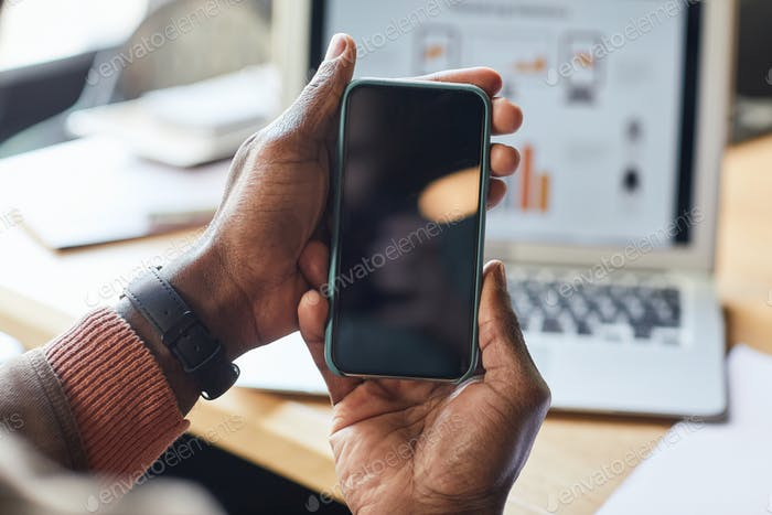 African Businessman Holding Mobile Phone Closeup