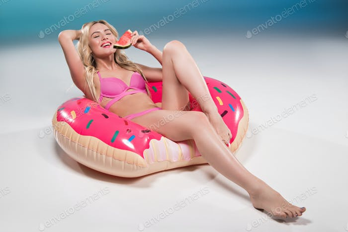 young woman in swimsuit eating watermelon while relaxing on float ring