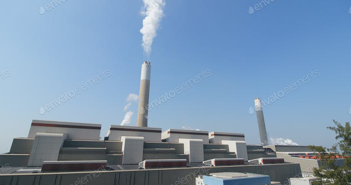 Industrial factory chimney and smoke over blue sky