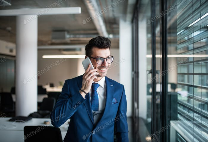 A portrait of young businessman with smartphone standing in an office.