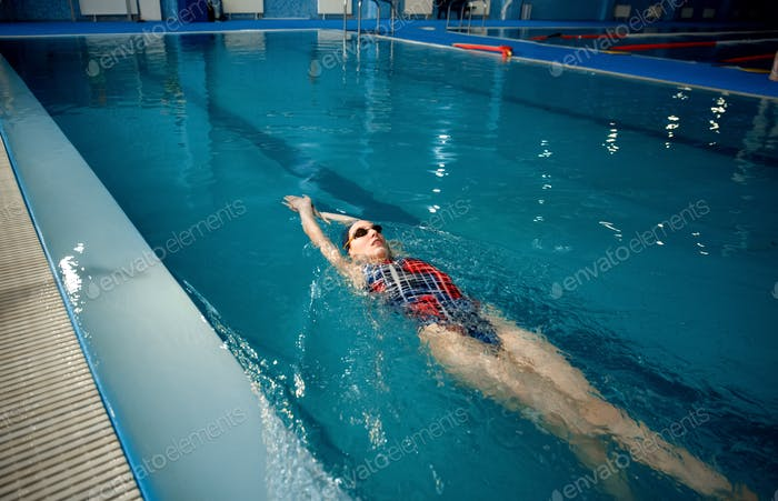 Female swimmer swimming on her back in pool