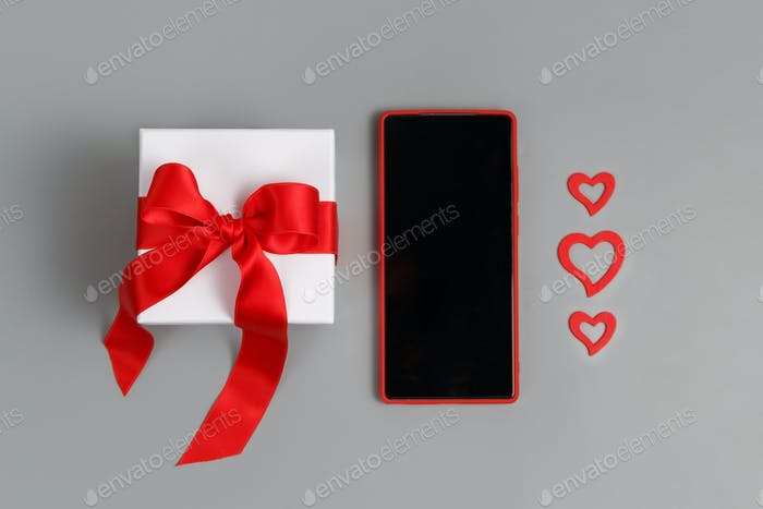 Placeit - Valentines Day concept - Red Mobile phone, gift box with a bow and hearts