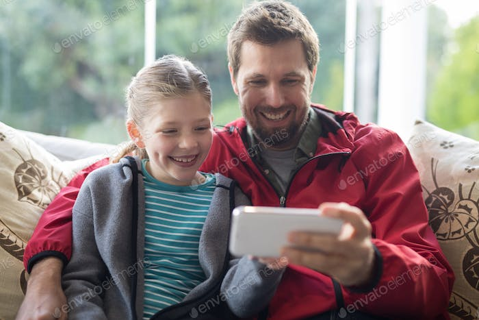Father and daughter using mobilephone