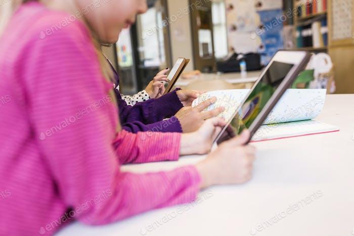 Girls (8-9) using digital tablets at school