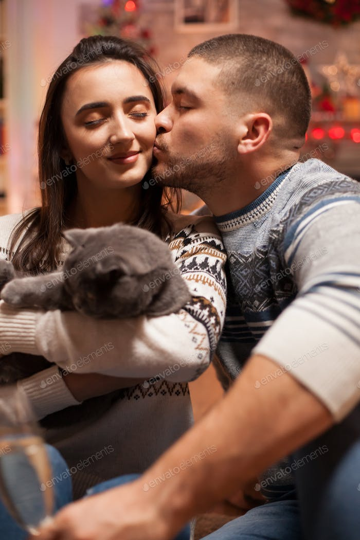 Boyfriend kissing his girlfriend cheek while holding the cat