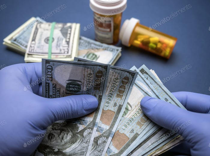 Doctor with blue latex gloves counting hundred dollar bills in a hospital