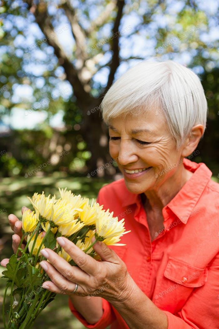 Lächelnde Senior Frau Blick auf gelbe Blumen