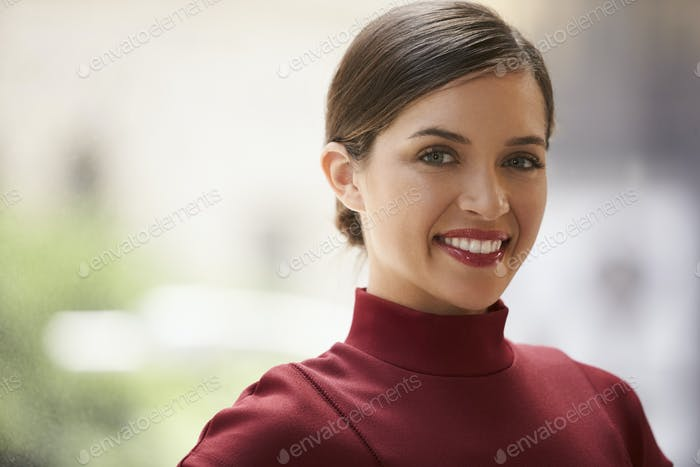 Head and shoulders portrait of young white businesswoman