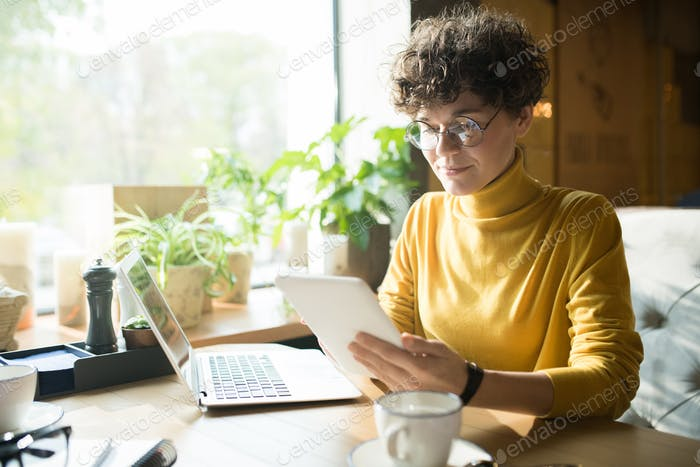 Content curly-haired freelancer analyzing online information