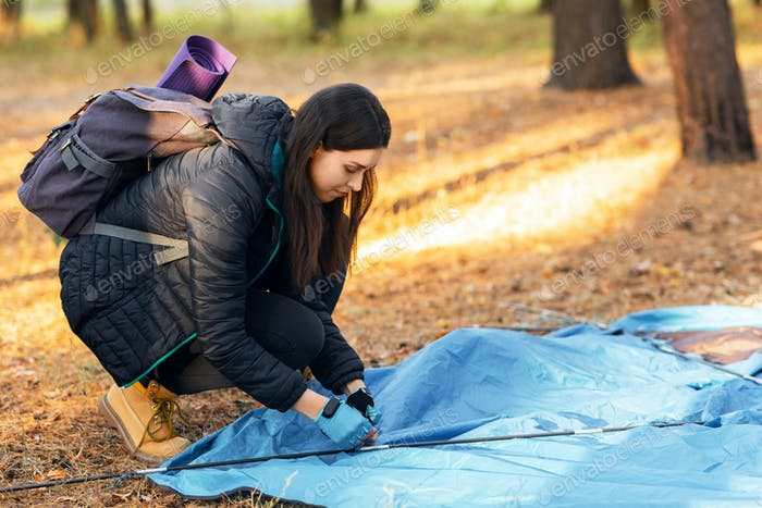 Young woman setting tent in camp, backpacking at countryside