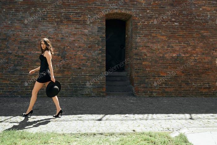 Элегантная женская модель в ходьбе возле кирпичной стены