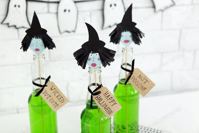 Close up of paper witches heads on the top of glass bottles