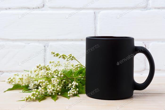Black coffee mug mockup with white spiraea flowers