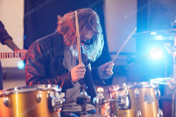 Long Haired Man Playing Drums in Stage Lights