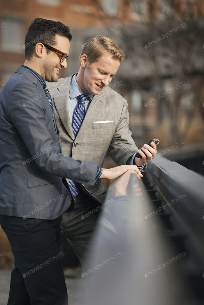Dos hombres de negocios mirando una pantalla de teléfono celular o teléfono móvil.