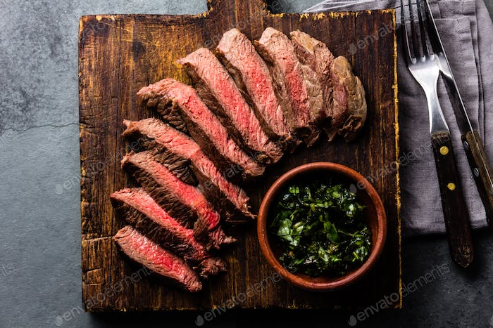 Slices of beef medium rare steak on wooden board, glass of red wine on slate background