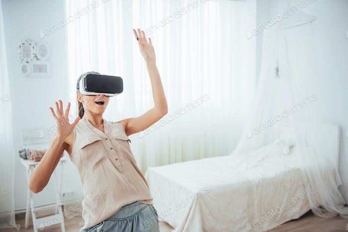 Frau bekommt Erfahrung mit VR-Brille Virtual Reality Headset in einem hellen Studio