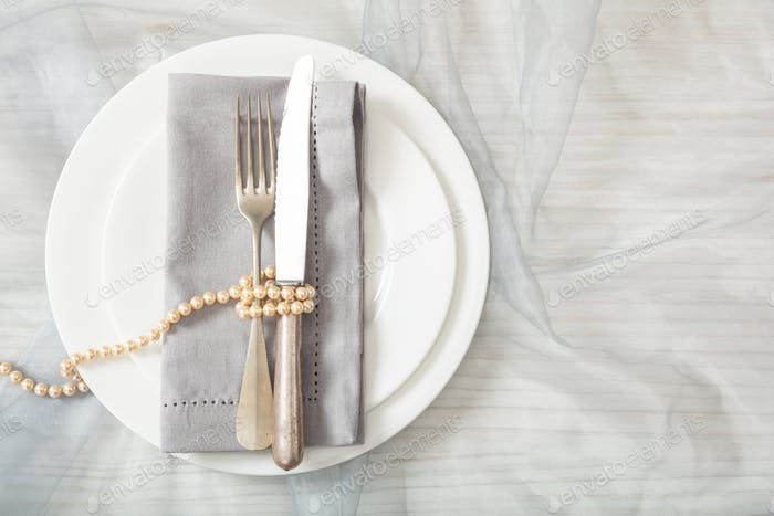 Wedding table place setting with plates, fork and knife, top view