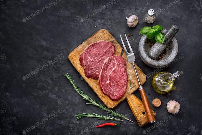 Raw steak with spices and ingredients