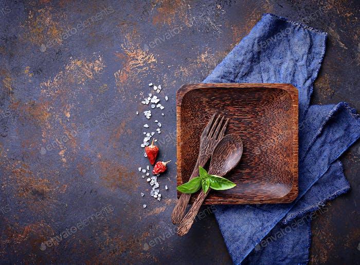 Leerer Holzteller, Besteck, Salz, Pfeffer und Basilikum