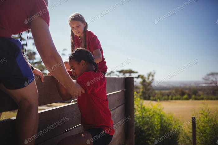 Trainer assisting kids to climb a wooden wall during obstacle course training