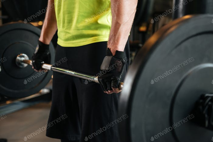 Cropped image of a sportsman holding heavy barbell