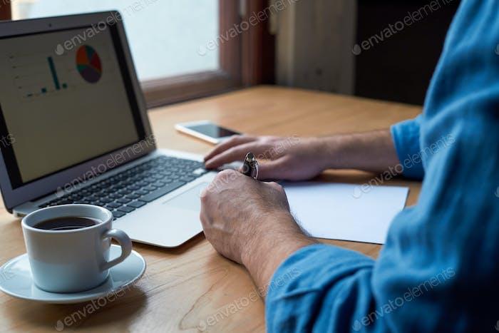 Unrecognizable man writes plan