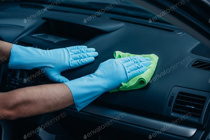 cropped view of car cleaner wiping dashboard with rag