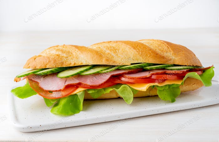 sandwich with ham, cheese, tomatoes, cucumbers, lettuce on white background