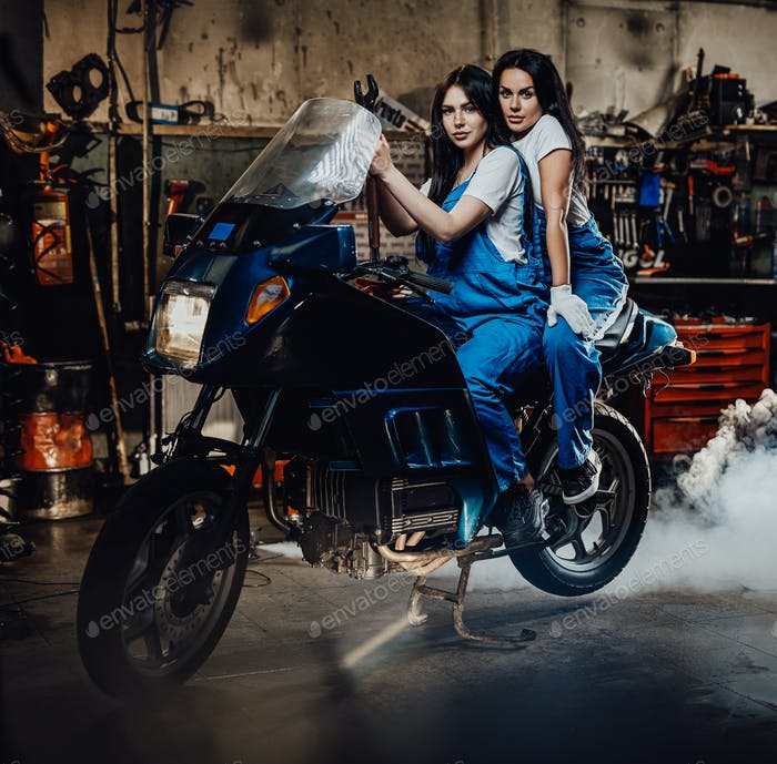 Two female mechanic sitting on sportbike in authentic workshop garage