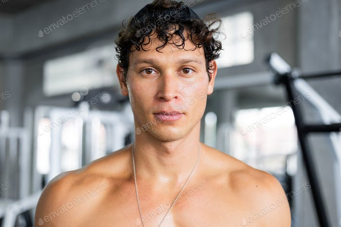 Portrait of topless athelete man at gym