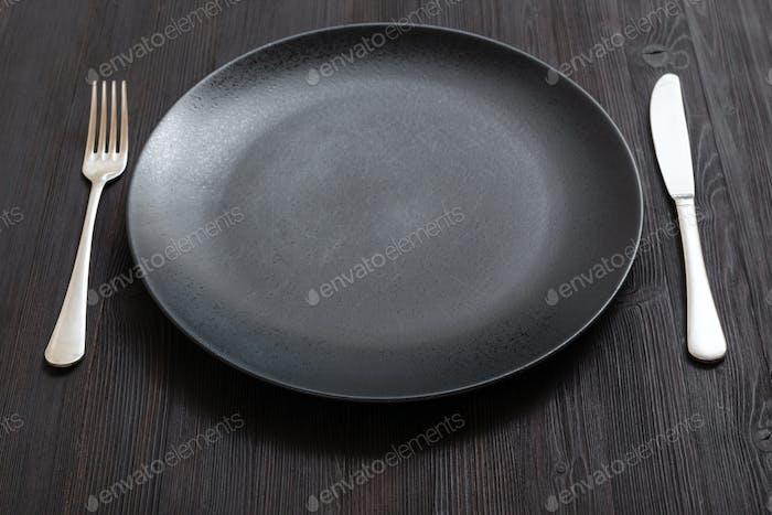 schwarzer Teller mit Messer, Löffel auf dunkelbraunem Tisch