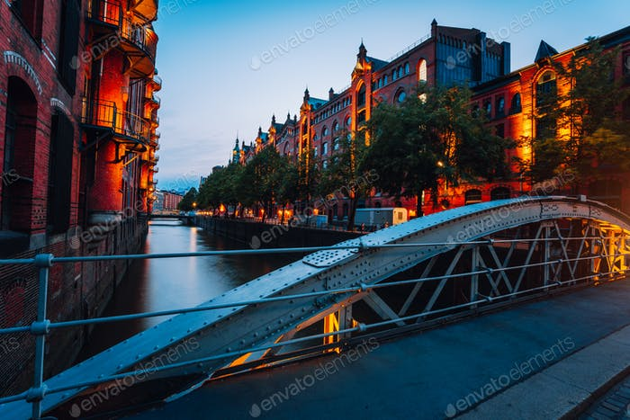Touristic spot of old bridge and red brick illuminated buildings, canal and square in golden sunset