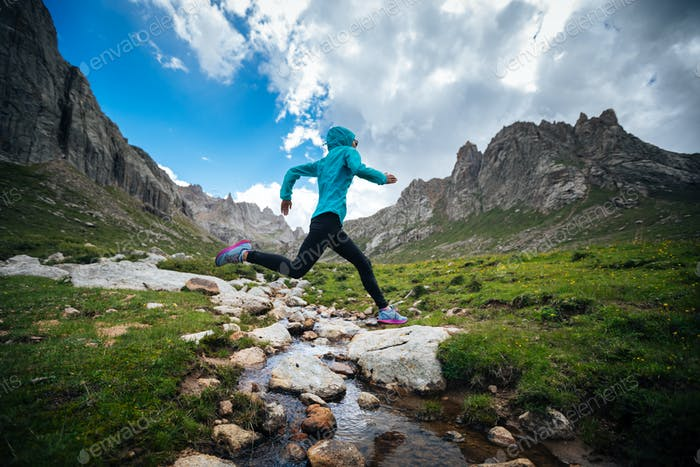 Woman trail runner jumping over small river on beautiful mountains